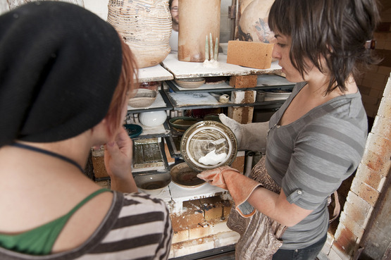 Two students looking at a ceramics piece together
