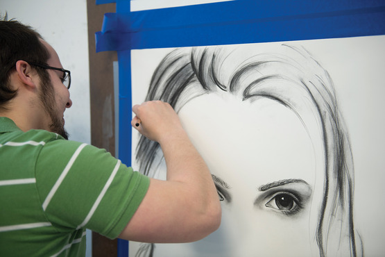 A student drawing a portrait of a woman