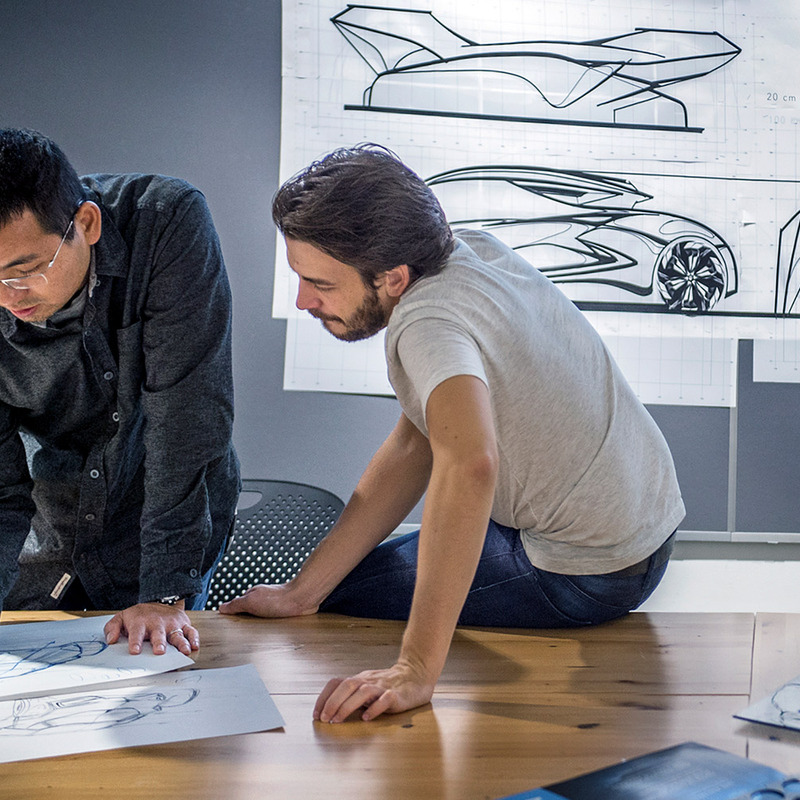 A professor helping a student with a car sketch