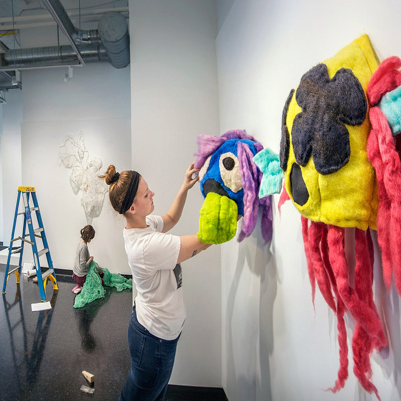 A student installing a show in the Student + Alumni Gallery