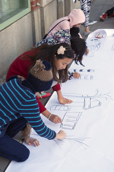 Young artists work together on a large group drawing.
