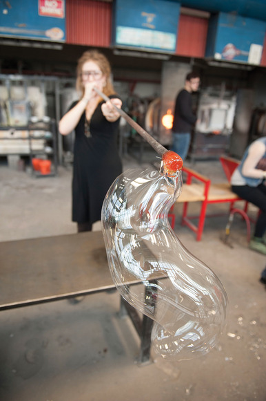 A student blowing glass