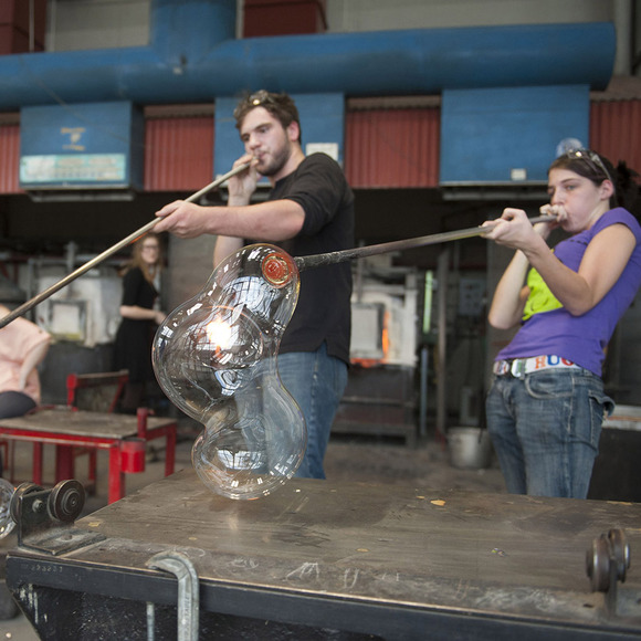 Image of student blowing glass
