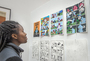 A high school student admiring illustrations done in the young artist cartooning class.