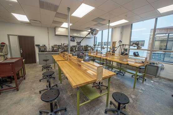 A studio classroom with a dedicated location for enamel work houses beautiful butcher-block benches that allow for intricate processes and clean space.