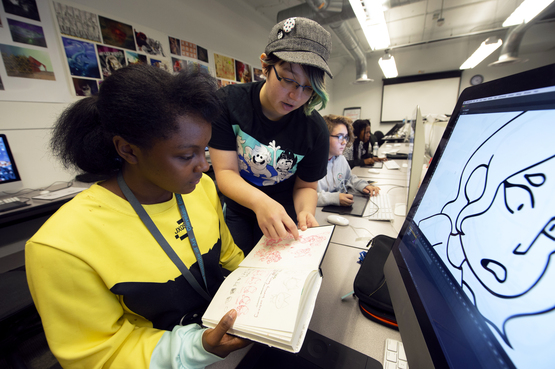 A Pre-College animation student and technical assistant look at sketches in the Animation lab.