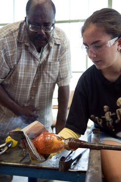 An instructor helps a student with their glass project.