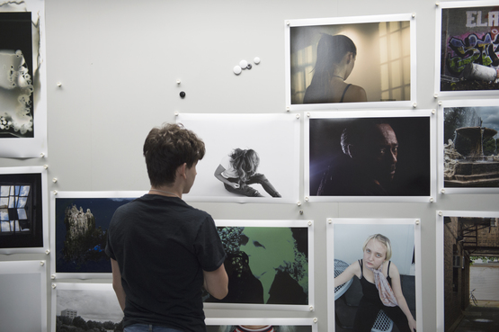A student stands in front of a wall where many photographs are pinned.