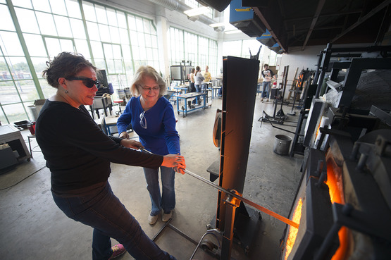 An instructor shows how to gather glass during a glassblowing workshop.
