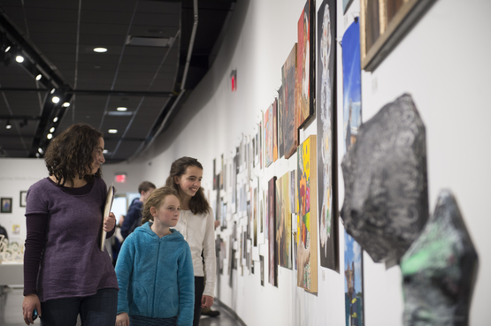 A student and their family view work displayed in the Scholastic Art and Writing exhibition.