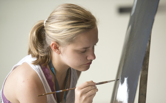 A student focuses intently on their painting.