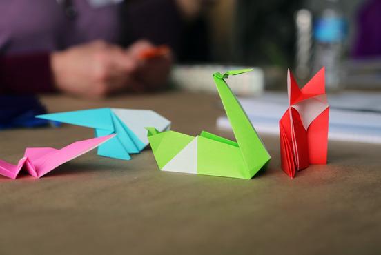 Folded paper pieces on display during an origami workshop.