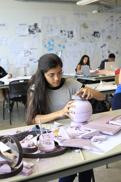 A student creating a 3D mock up using carved foam.