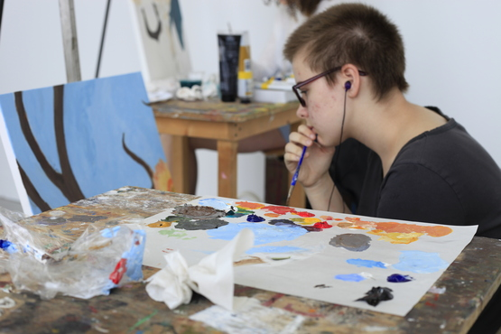 A student working on a painting, with their color palette laid out next to them.