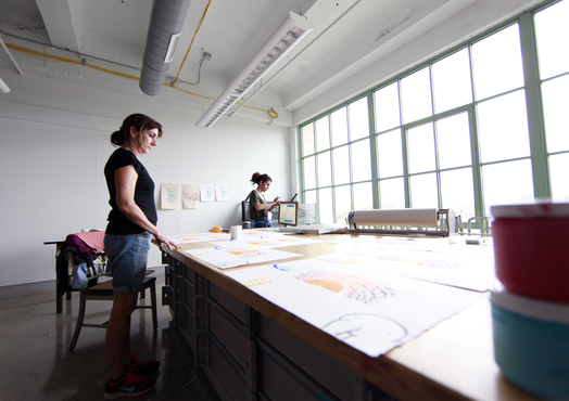 A student lays out their prints in the printmaking shop.