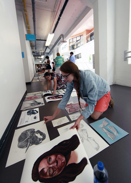 Biomedical students lay out their work and prepare for installation for the Pre-College exhibition.