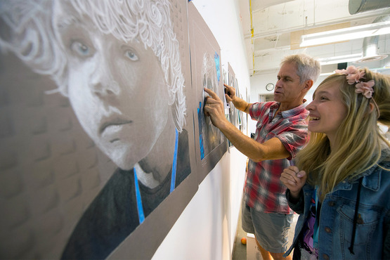 A student installs their work for the Pre-College exhibition with help from their instructor.