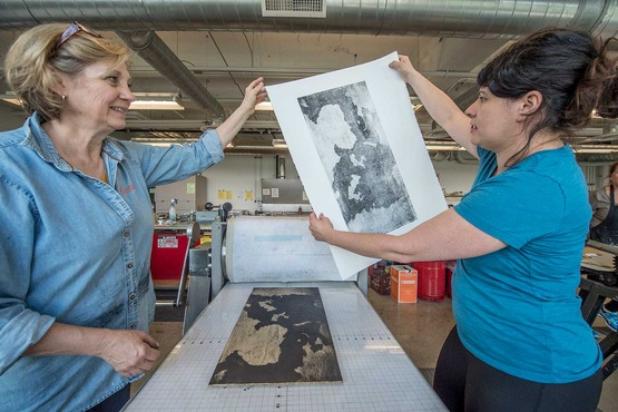 Two teachers admire a paper lithography print.