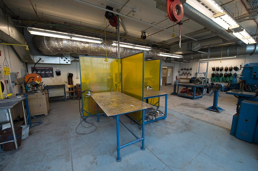 Metal shop equipment includes welding tables, a cold saw, and vertical band saw for metal.