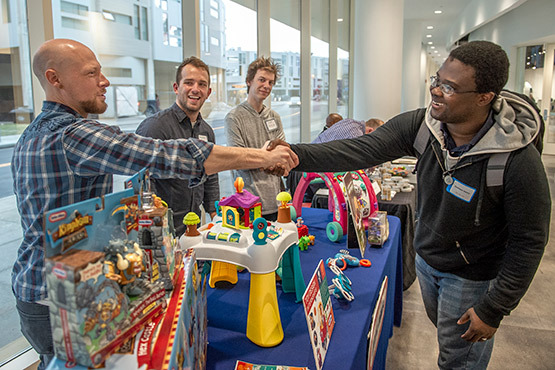 A student shaking hands with an employer from Little Tikes at a career fair.
