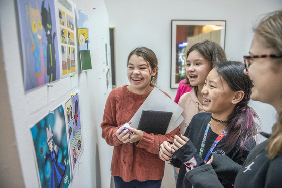 Young students looking at artwork at the Young Artists reception