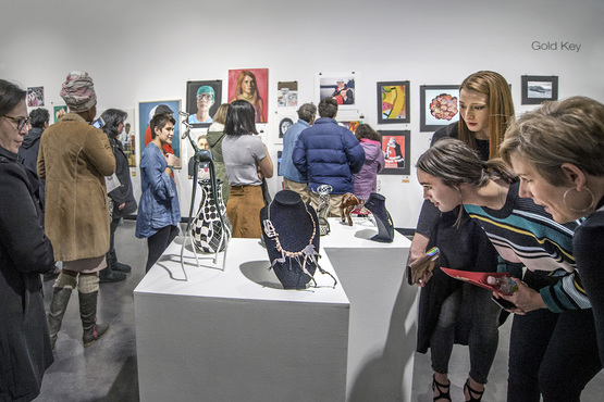 Students and their families admiring work on display during the Scholastic Art and Writing reception.