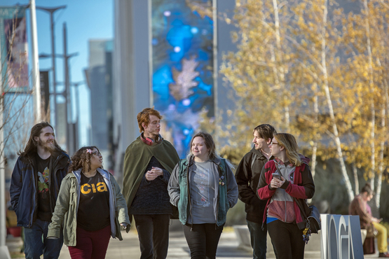 students walking through Uptown neighborhood in fall